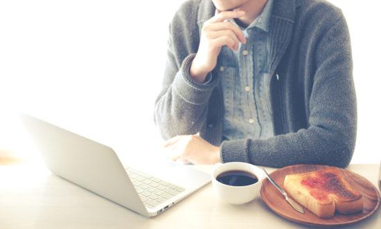 朝ご飯を食べながらパソコンを見ている男性
