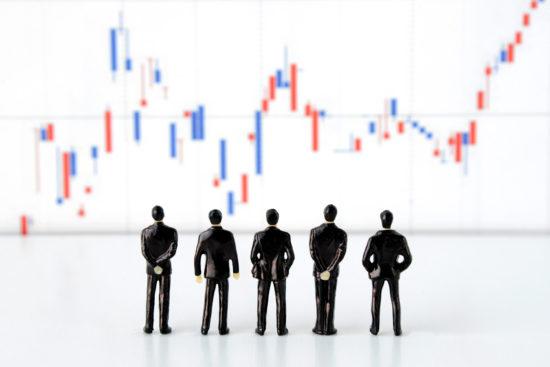 株価チャートを眺める数体の人形