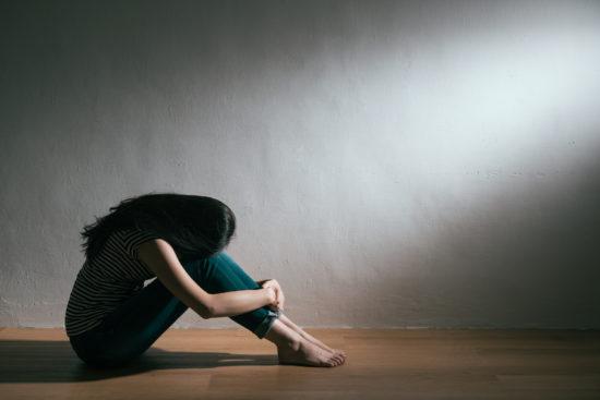 絶望に顔を覆い座り込む女性
