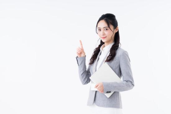人差し指を立てたスーツを着た若い女性