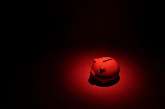 暗闇の中で赤く輝く豚の貯金箱