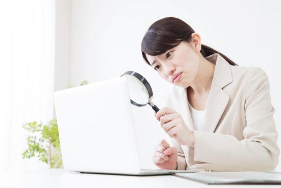 ルーペでノートパソコンを覗きながら慎重にチェックしようとするスーツを着た女性