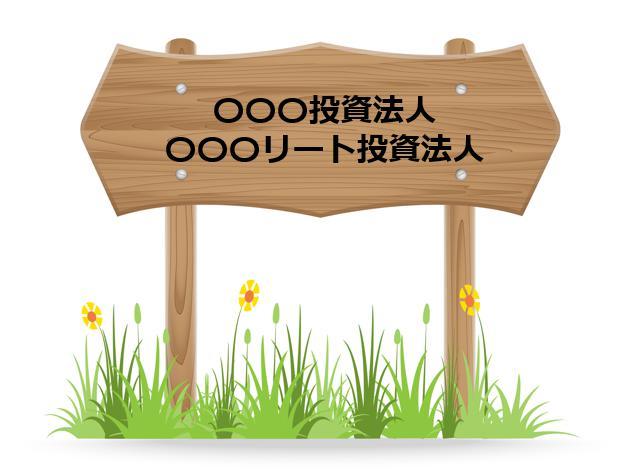 投資法人やリート投資法人と言う文字が書かれた足元に草花が生えた木の案内看板