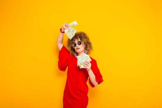 富裕層を表すオレンジ背景にお金をつらつかせる赤い服を着た女性