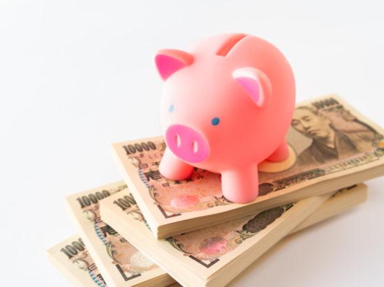 札束の上にのったピンクの豚の貯金箱